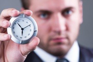 40893594 - adult serious businessman shows a little white clock
