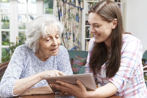 46634489 - teenage granddaughter showing grandmother how to use digital tablet