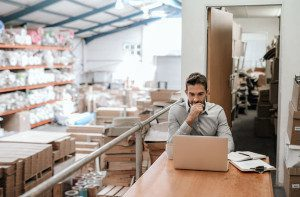Manager working online while sitting in a warehouse office